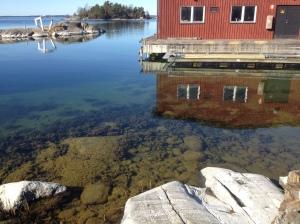En stilla morgon vid Askö båthus med kristallklart vatten.